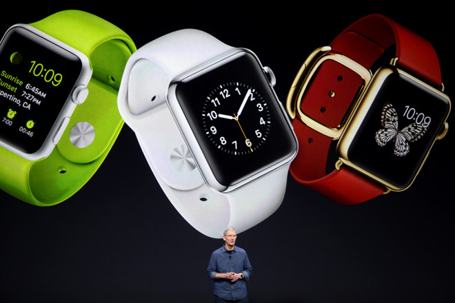 A man standing in front of a screen showing three models of the Apple Watch