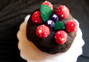 image showing a cake made out of felt; vanilla cake with dark brown icing; strawberries and blueberries on top