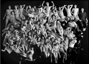 "Mostly white people, lying all piled up on the floor, in underwear or ""nude"" colored bodysuits. A few clothed people are also shown in the ""pile."""