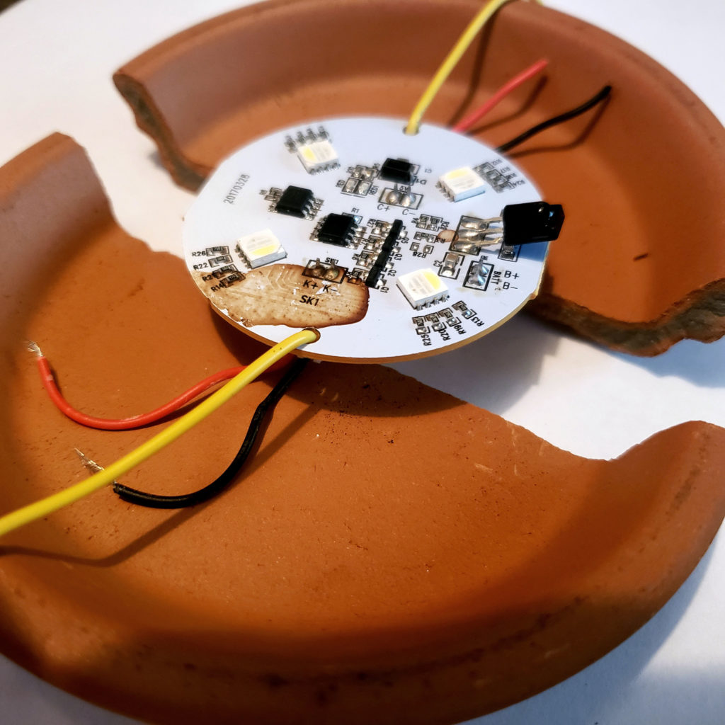 Terra-Cotta plate shattered in half, bound by a micro-chip and serial wires. Loose power and ground wires are on each side.