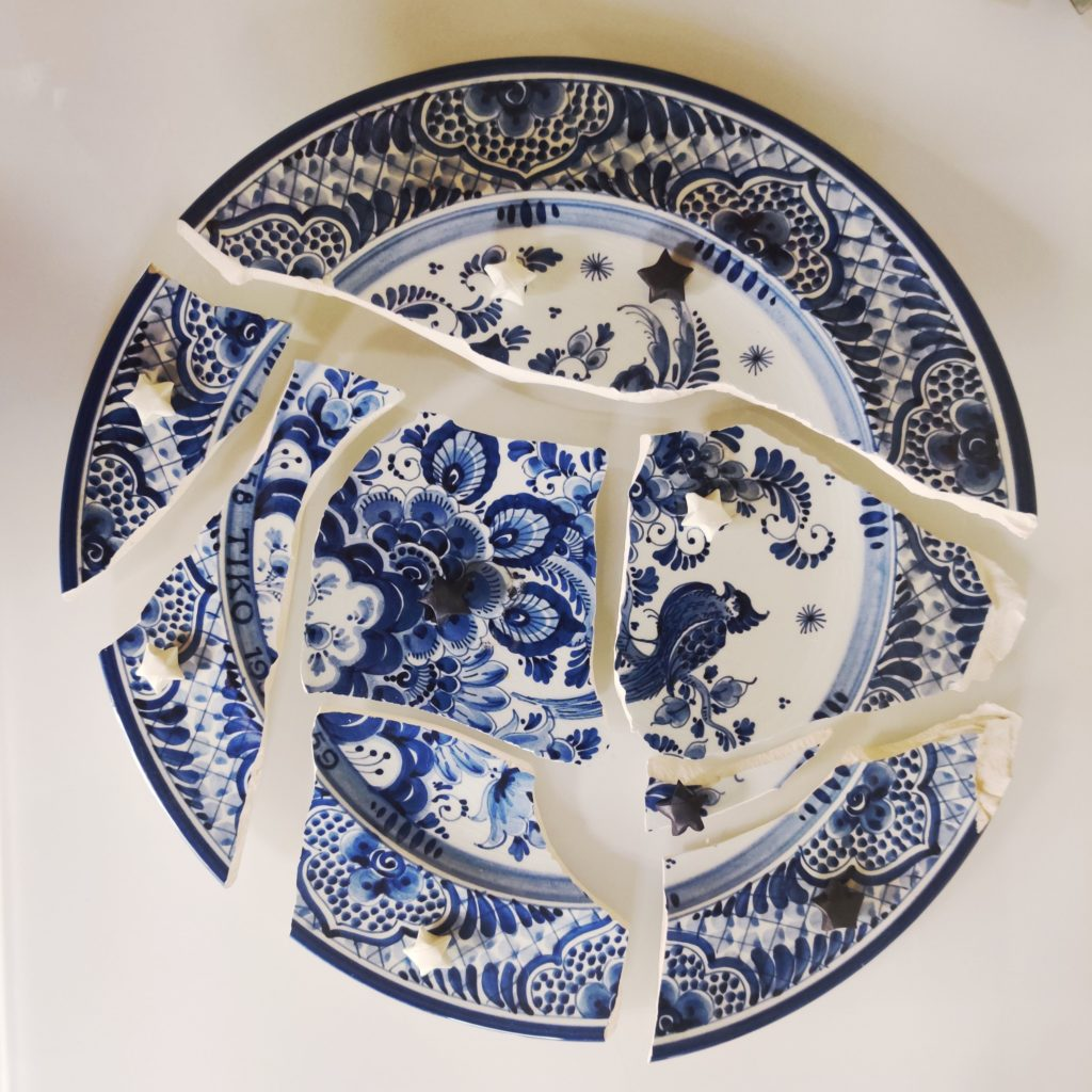 Shattered Blue and white porcelain plate with white and black paper stars placed around it.