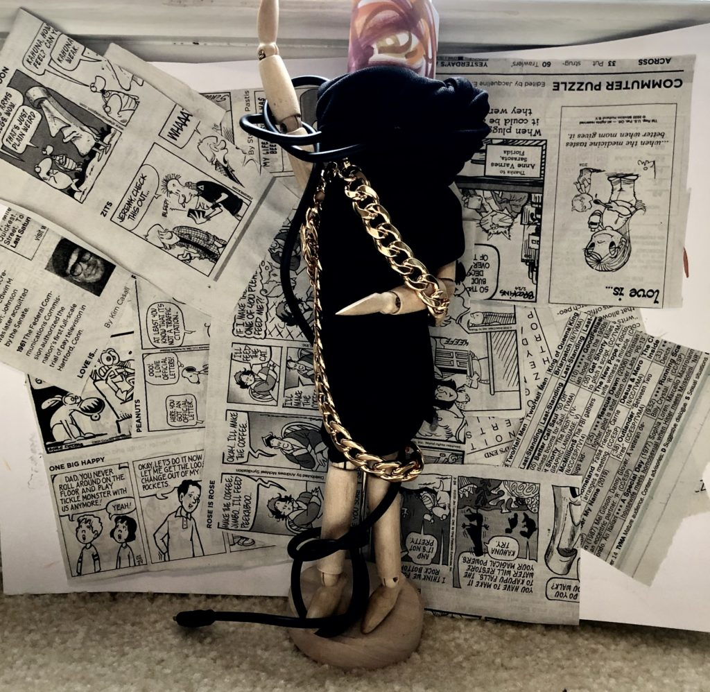 : Wooden figure wrapped in black cloth. gold chain and power cord entangled with cloth. newspaper clippings of comic strips are behind wooden figure